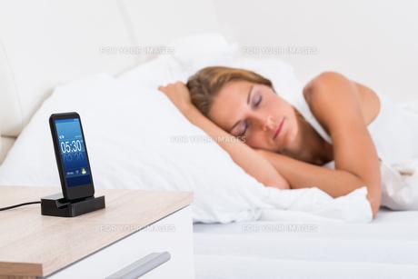 Woman Sleeping With Alarm On Mobile Phoneの写真素材 [FYI00789555]