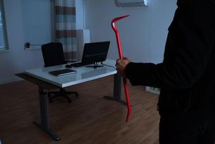 Burglar With Crowbar In Officeの写真素材 [FYI00789560]