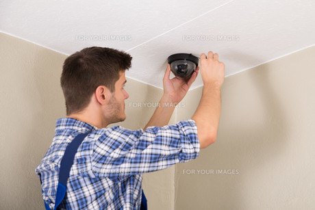 Technician Installing Surveillance Cameraの写真素材 [FYI00789584]