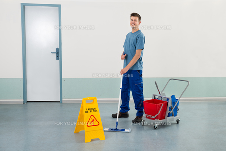 Male Worker With Cleaning Equipments Mopping Floorの写真素材 [FYI00789592]