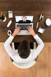 Businessman Videochatting With Senior Colleagueの写真素材 [FYI00789596]