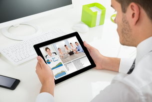Businessman Videoconferencing With Colleagues On Digital Tabletの写真素材 [FYI00789604]