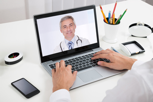 Businessperson Videochatting With Doctor On Laptopの写真素材 [FYI00789614]