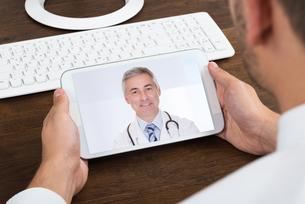 Businessperson Videochatting With Senior Doctorの写真素材 [FYI00789621]