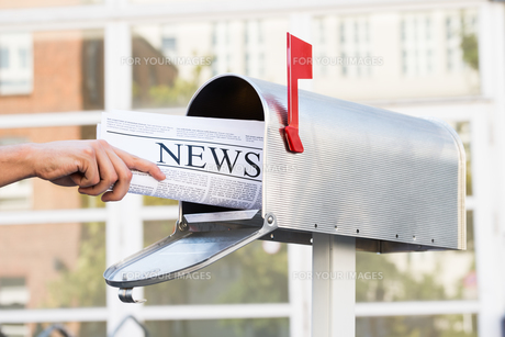 Person Hands Opening Mailbox To Remove Newspaperの素材 [FYI00789668]