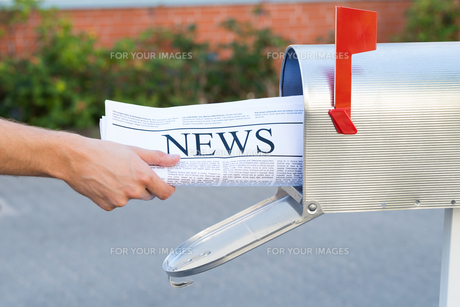 Person Hands Opening Mailbox To Remove Newspaperの素材 [FYI00789678]