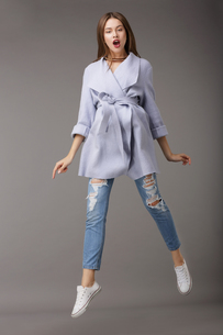 Trendy Young Female Jumping in Blue Coatの写真素材 [FYI00789883]
