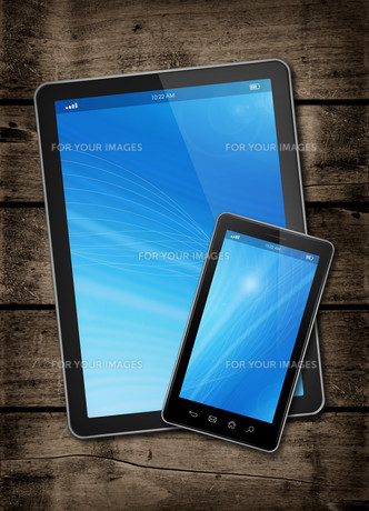 Smartphone and digital tablet PC on a dark wood tableの写真素材 [FYI00790226]