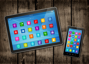 Smartphone and digital tablet PC with desktop icons on a dark wood tableの写真素材 [FYI00790240]