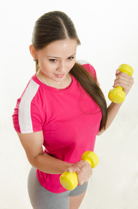 The girl is engaged in fitness with two dumbbellsの写真素材 [FYI00790306]