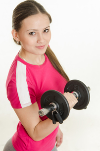 Girl athlete looking up holding a dumbbell in her handの写真素材 [FYI00790314]