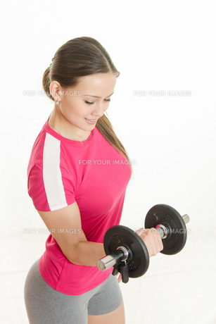 Sportswoman looking at dumbbell in the right handの写真素材 [FYI00790322]
