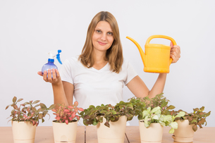 The girl is holding a spray bottle and a watering can to care for flowersの写真素材 [FYI00790341]