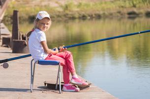 Girl fishing sitting on a chair on the bridgeの写真素材 [FYI00790349]