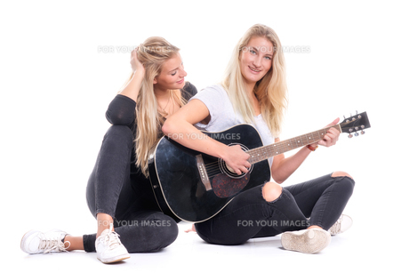 2 young girl sitting on the floor and playing guitarの写真素材 [FYI00790986]