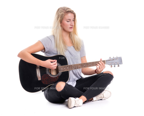 young girl sitting cross-legged and playing guitarの写真素材 [FYI00790988]