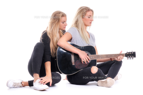 blonde girl listening to her sister playing the guitar toの写真素材 [FYI00791010]