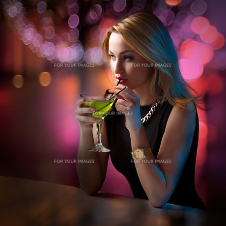 Woman sipping her cocktail while looking aroundの写真素材 [FYI00791087]