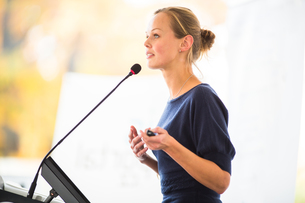Pretty, young business woman giving a presentation in a conference/meeting setting (shallow DOF  color toned image)の素材 [FYI00791363]