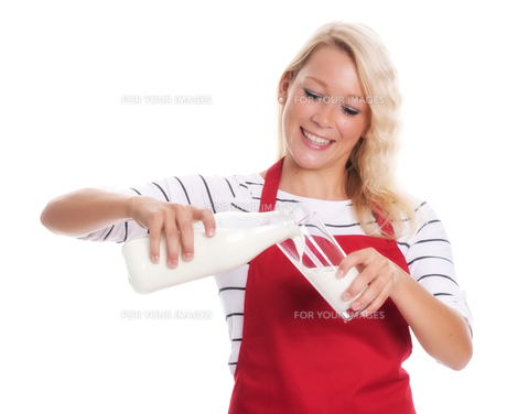 housewife in apron pouring milk into a glassの素材 [FYI00791593]