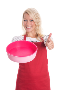 woman in apron holding a silicone mold and showing thumbs upの写真素材 [FYI00791607]