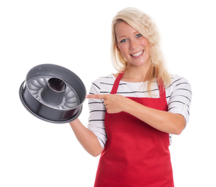 housewife in apron pointing at a cake moldの写真素材 [FYI00791615]