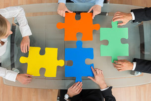 Businesspeople With Jigsaw Pieces At Deskの写真素材 [FYI00791875]