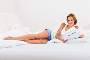 Woman In Bed With Newspaperの写真素材 [FYI00791967]