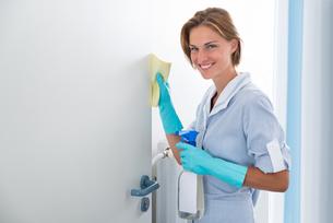 Young Maid Cleaning Doorの写真素材 [FYI00791988]