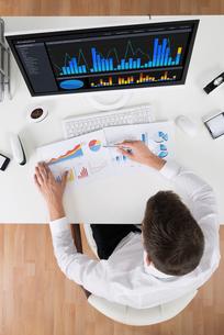 Businessman Analyzing Statistical Graphsの写真素材 [FYI00791990]