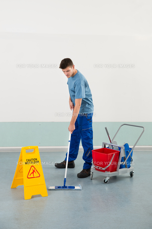 Male Worker With Cleaning Equipments Mopping Floorの写真素材 [FYI00792009]