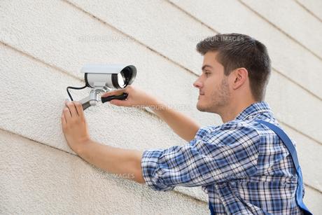 Technician Fixing Cctv Camera On Wallの素材 [FYI00792012]