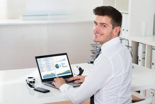 Businessman Analyzing Financial Statistics On Laptopの写真素材 [FYI00792025]