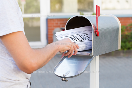 Person Hands Opening Mailbox To Remove Newspaperの素材 [FYI00792061]