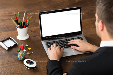 Businessman With Office Supplies Working On Laptopの写真素材 [FYI00792072]