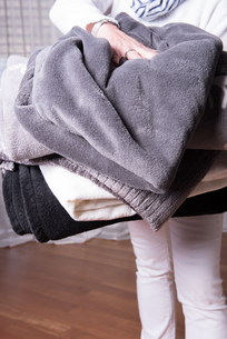 female helper welcomes refugees with warm blankets for cold nightsの素材 [FYI00792318]