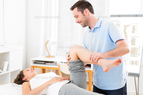 Young attractive woman being manipulated by physiotherapistの素材 [FYI00792469]
