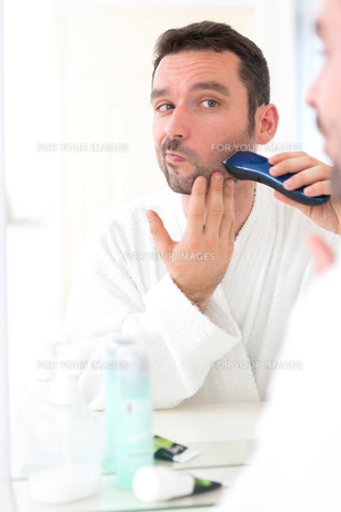 Young attractive man shaving his beard in front of a mirrorの素材 [FYI00792517]
