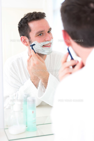 Young attractive man shaving his beard in front of a mirrorの素材 [FYI00792531]