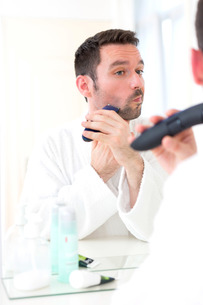 Young attractive man shaving his beard in front of a mirrorの素材 [FYI00792532]