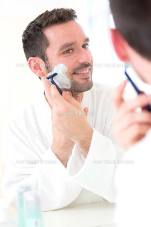 Young attractive man shaving his beard in front of a mirrorの素材 [FYI00792533]