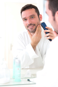 Young attractive man shaving his beard in front of a mirrorの素材 [FYI00792534]