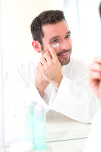 Young attractive man applying anti dark circles cream around eyesの素材 [FYI00792538]