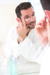 Young attractive man applying anti dark circles cream around eyesの素材 [FYI00792539]