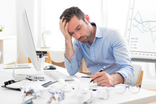 Young attractive man too tired to workの写真素材 [FYI00792541]