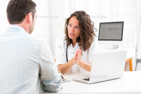 Young attractive doctor listening his patientの素材 [FYI00792544]