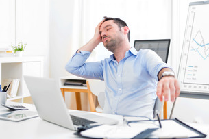 Young attractive man too tired to workの写真素材 [FYI00792545]
