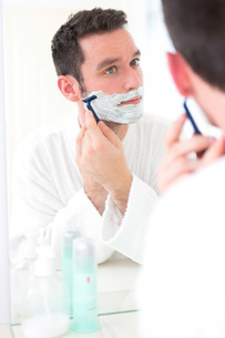 Young attractive man shaving his beard in front of a mirrorの素材 [FYI00792546]