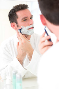 Young attractive man shaving his beard in front of a mirrorの素材 [FYI00792547]