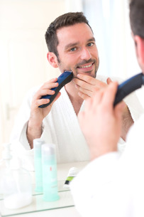 Young attractive man shaving his beard in front of a mirrorの素材 [FYI00792549]